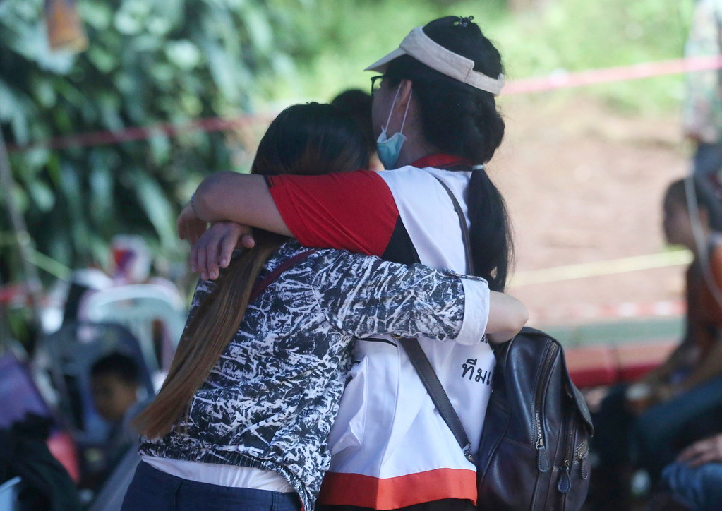 . A family member, left, and a Thai official hug each other near a cave where 12 boys and their soccer coach are trapped, in Mae Sai, Chiang Rai province, in northern Thailand, Thursday, July 5, 2018. A Thai official overseeing the rescue operation of the soccer team trapped in the flooded cave said they may not all be extracted at the same time depending on their health. (AP Photo/Sakchai Lalit)