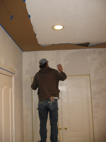 Stripping the wallpaper left a rough surface, unsuitable for painting, so Tony masked off everything but the walls in preparation for spraying on a thinned drywall mud mixture.