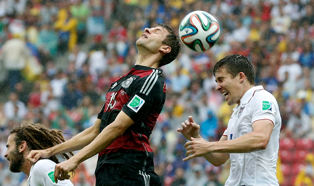 . Germany\'s Thomas Mueller and United States\' Matt Besler, right, go for a header during the group G World Cup soccer match between the USA and Germany at the Arena Pernambuco in Recife, Brazil, Thursday, June 26, 2014. (AP Photo/Matthias Schrader)