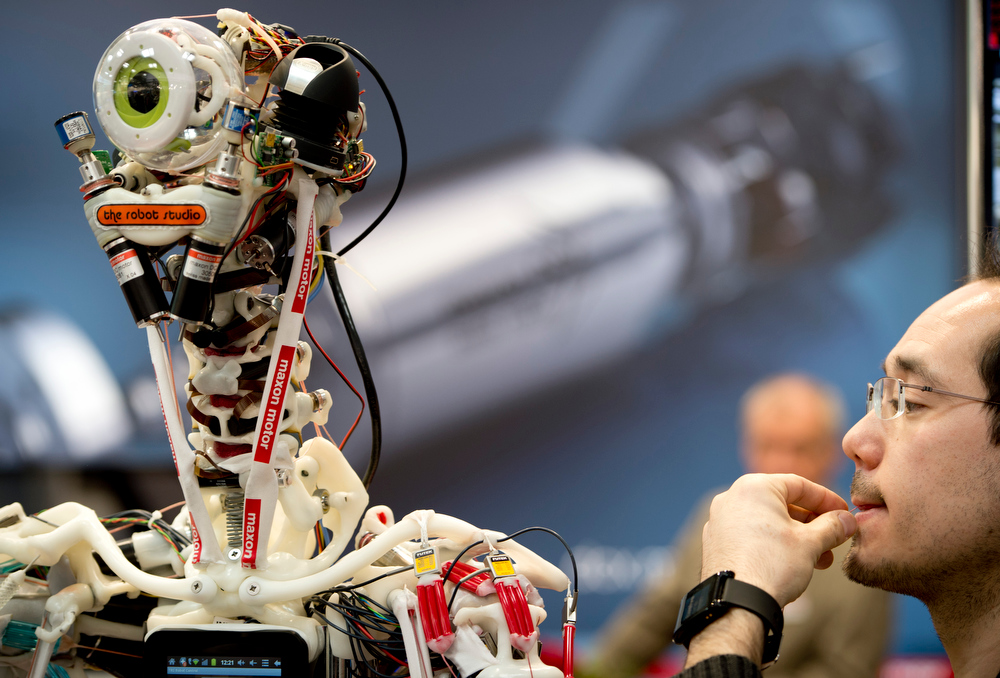 Description of . A technician performs electronic surgery by replacing a thin cable on a robot at tMaxon's booth at the industrial trade fair in Hanover, central Germany on April 8, 2013. The fair running from April 8 to 12, 2013 presents a cross section of key industrial technologies. ODD ANDERSEN/AFP/Getty Images