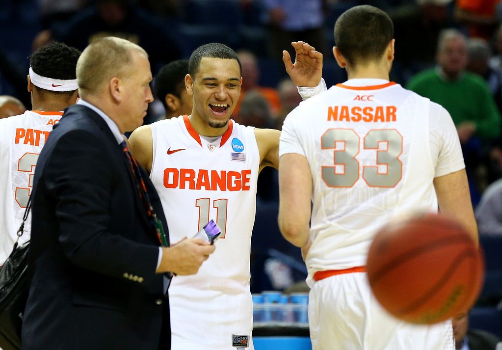 . BUFFALO, NY - MARCH 20: Tyler Ennis #11 celebrates with Albert Nassar #33 of the Syracuse Orange after defeating the Western Michigan Broncos 77-53 during the second round of the 2014 NCAA Men\'s Basketball Tournament at the First Niagara Center on March 20, 2014 in Buffalo, New York.  (Photo by Elsa/Getty Images)