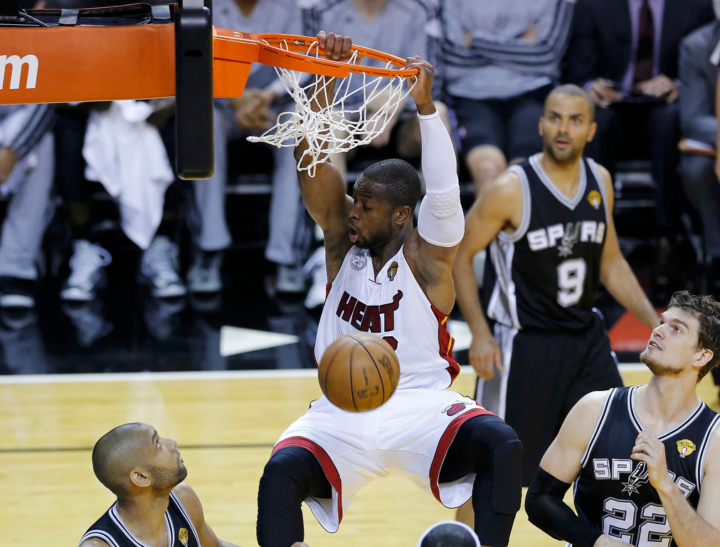 . Miami Heat\'s Dwyane Wade dunks over San Antonio Spurs\' Tim Duncan (L) and Tiago Splitter (R) during the first quarter in Game 1 of their NBA Finals basketball playoff in Miami, Florida June 6, 2013. REUTERS/Joe Skipper