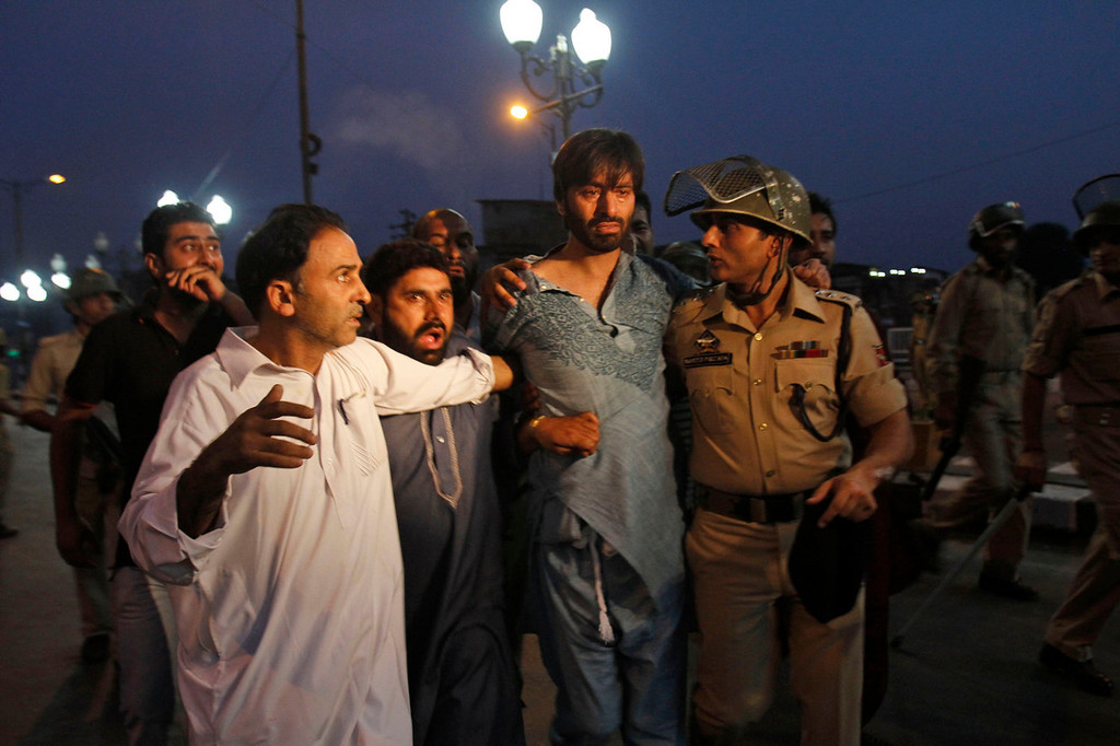 . An Indian police officer detains Kashmiri separatist leader Yasin Malik, center, during a protest after paramilitary troops fired on a civilian when he allegedly failed to stop the car he was driving at a police barricade in Srinagar, India, Saturday, Sept. 7, 2013. A protest erupted Saturday after Indian police said they killed two alleged militants and two civilians in the disputed Himalayan territory of Kashmir, while authorities maintained tight security for a classical music concert being staged amid separatist objections. The driver was hospitalized in critical condition. (AP Photo/Mukhtar Khan)