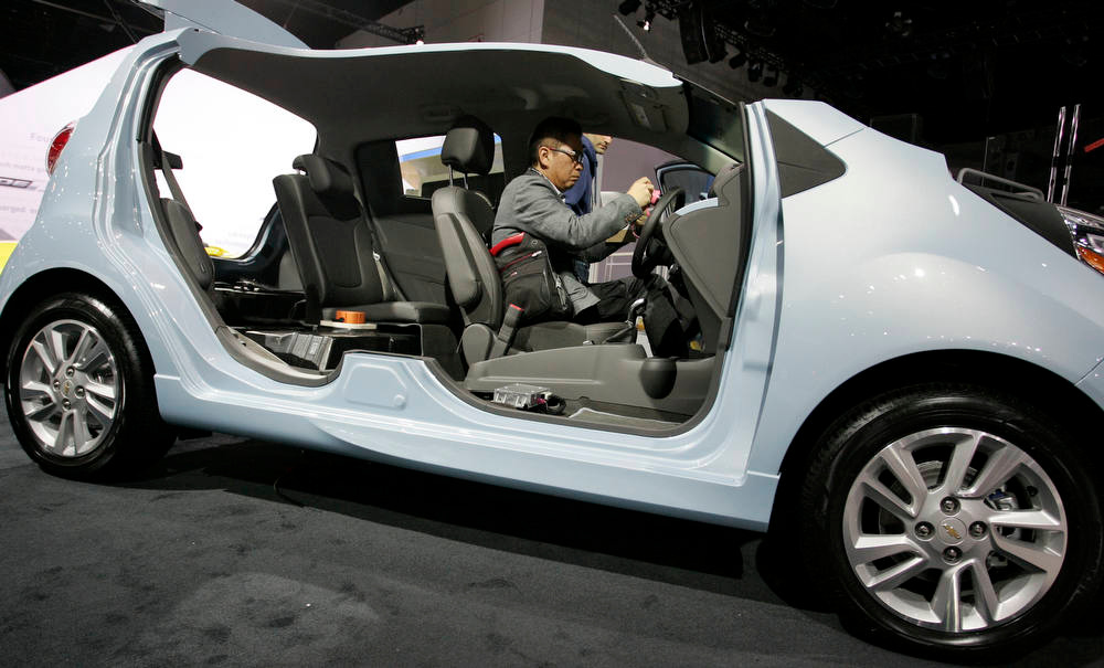 . An attendee sits inside a display vehicle at the General Motors Co. Chevrolet stand during the LA Auto Show in Los Angeles, California, U.S., on Wednesday, Nov. 28, 2012. The LA Auto Show is open to the public Nov. 30 through Dec. 9. Photographer: Jonathan Alcorn/Bloomberg