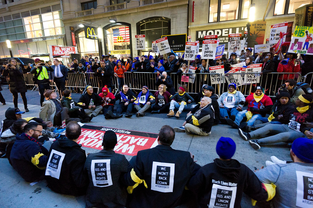 . A crowd of about 350 protesters stand on Broadway in front of a McDonald\'s restaurant, Tuesday, Nov. 29, 2016, in New York. About 25 of the chanting minimum-wage protesters, foreground, were arrested. The event was part of the National Day of Action to Fight for $15. The campaign seeks higher hourly wages, including for workers at fast-food restaurants and airports. (AP Photo/Mark Lennihan)