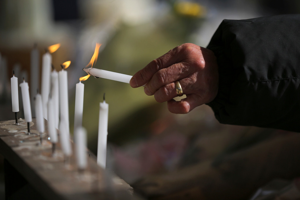 . FILE - In this March 11, 2015, file photo, a woman lights a candle in prayer to mourn for victims of earthquake and tsunami during a special memorial event in Tokyo. Still struggling to recover, the tsunami-hit region of northeastern Japan marked the fourth anniversary of the disaster Wednesday with simultaneous moments of silence along the coast. (AP Photo/Eugene Hoshiko, File)