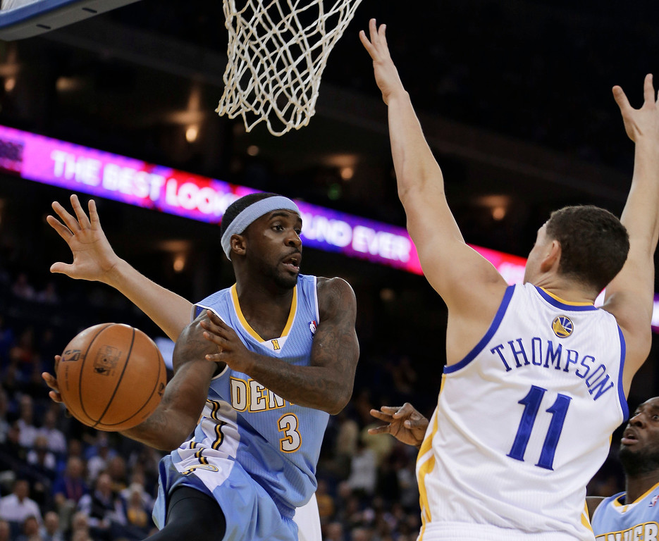 . Denver Nuggets\' Ty Lawson, left, looks to pass away from Golden State Warriors\' Klay Thompson (11) during the first half of an NBA basketball game Wednesday, Jan. 15, 2014, in Oakland, Calif. (AP Photo/Ben Margot)