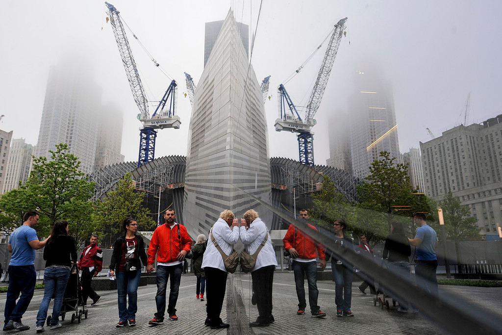 . Members of the general public are reflected in the glass facade of the 9/11 Memorial Museum pavilion during the dedication ceremony at the National September 11 Memorial Museum in New York on Thursday,  May 15, 2014. (AP Photo/Anthony Behar, Pool)