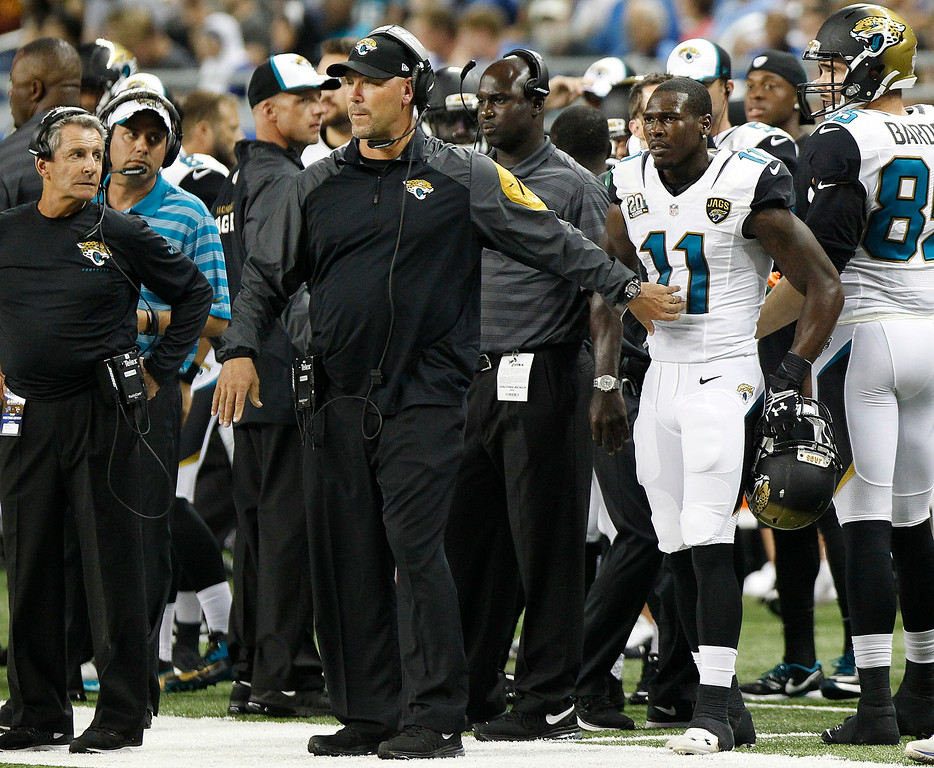 . Jacksonville Jaguars head coach Gus Bradley holds back  wide receiver Marqise Lee (11) on the sideline after a penalty against the Detroit Lions in the first half of a preseason NFL football game at Ford Field in Detroit, Friday, Aug. 22, 2014.  (AP Photo/Duane Burleson)