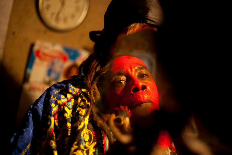 . In this Jan. 27, 2013 photo, snake handler Saintilus Resilus looks in the mirror as he paints his face red before performing with snakes for money during the pre-Lenten Carnival season at his home in Petionville, Haiti. It\'s the serpents that help him eat and pay rent, in addition to his work for a neighborhood herbologist. And it\'s the snakes for which he\'s most famous. (AP Photo/Dieu Nalio Chery)
