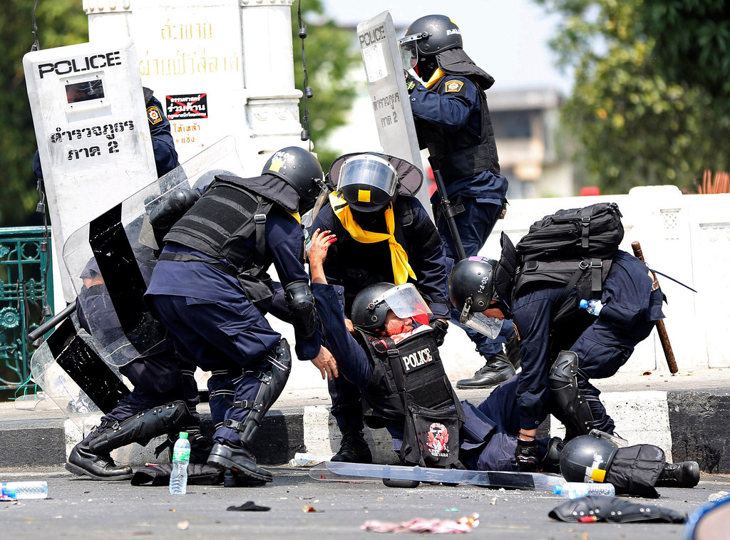 . An injured Thai police officer, center bottom, is helped by colleagues after a bomb blast near them during a clash with anti-government protesters Tuesday, Feb. 18, 2014 in Bangkok, Thailand. (AP Photo/Apichart Weerawong)