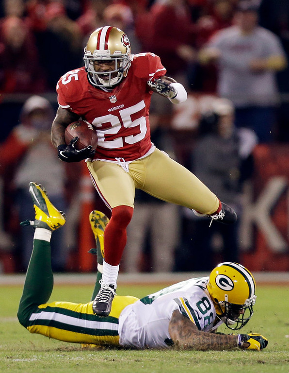 . San Francisco 49ers cornerback Tarell Brown (25) returns an interception from Green Bay Packers quarterback Aaron Rodgers as he leaps over Green Bay Packers tight end Jermichael Finley (88) in the first half of an NFC divisional playoff NFL football game in San Francisco, Saturday, Jan. 12, 2013. (AP Photo/Marcio Jose Sanchez)