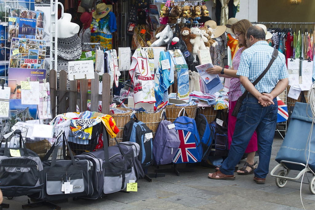""". Tourists look at store goods on Casemates square in Gibraltar on August 13, 2013 as Spain today enforced tight border checks in a growing row with Britain over the tiny territory and its surrounding waters. On the \""""Rock\"""" itself, defiant residents declared themselves thoroughly British, surrounded by English pubs serving fish and chips, Royal Mail letter boxes, bright red telephone cabins and the occasional monkey.    MARCOS MORENO/AFP/Getty Images"""