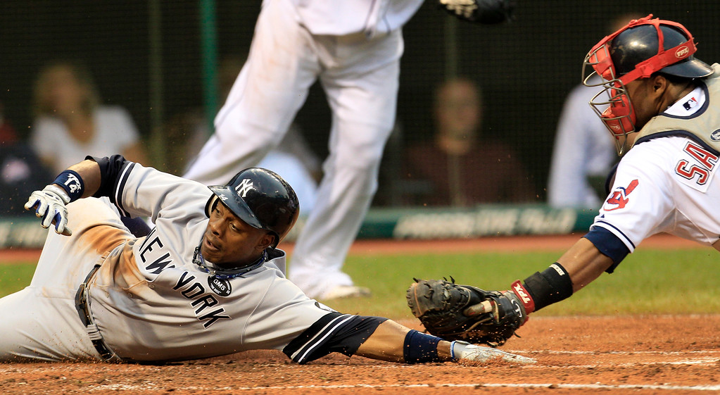 . New York Yankees\' Curtis Granderson slides safely into home plate as Cleveland Indians catcher Carlos Santana is late on the tag in the second inning in a baseball game Wednesday, July 28, 2010, in Cleveland. Granderson scored on a single by Brett Gardner. (AP Photo/Tony Dejak)