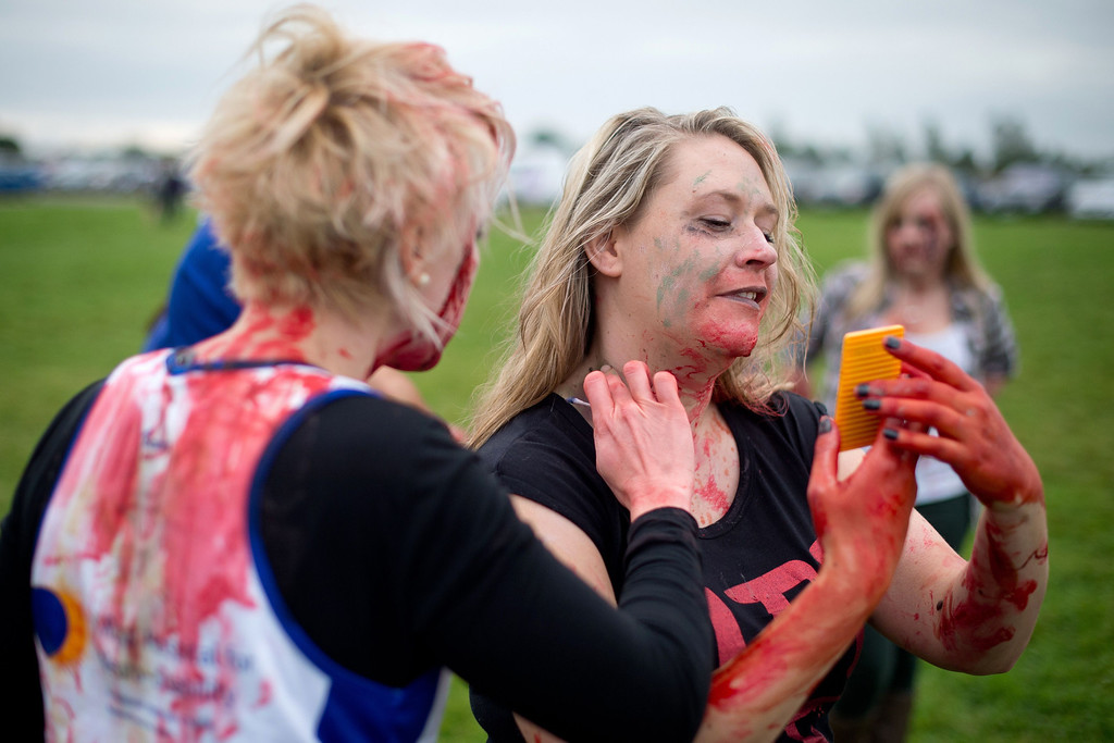 """. Volunteer \""""zombies\"""" prepare to take part in one of Britain\'s biggest horror events, the \""""Zombie Evacuation Race\"""" at Carver Barracks near Saffron Walden, England, on October 5, 2013. The race sees thousands of participants attempt to complete a gruelling 5 kilometre cross-country run, while evading \""""zombies\"""", intent on snatching the three life-line strips hanging from every runner\'s waist.  Those who manage to get through with any strips remaining are named as survivors while those without take home an \""""infected\"""" badge.  LEON NEAL/AFP/Getty Images"""