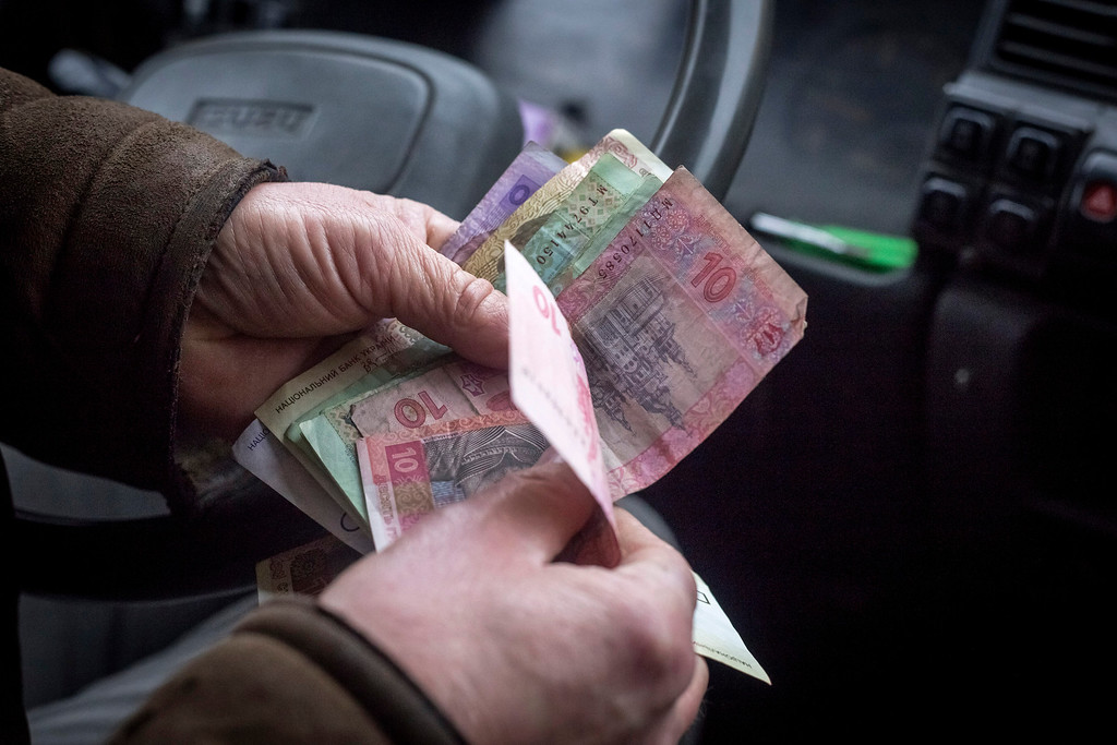 . A taxi driver counts out hyrvnia banknote in payment for a fare in Kiev, Ukraine, on Tuesday, March 4, 2014. Moscow\'s move to seize control of the Black Sea region triggered a sell-off in global equities and currencies from Russia to Turkey yesterday. Photographer: Vincent Mundy/Bloomberg