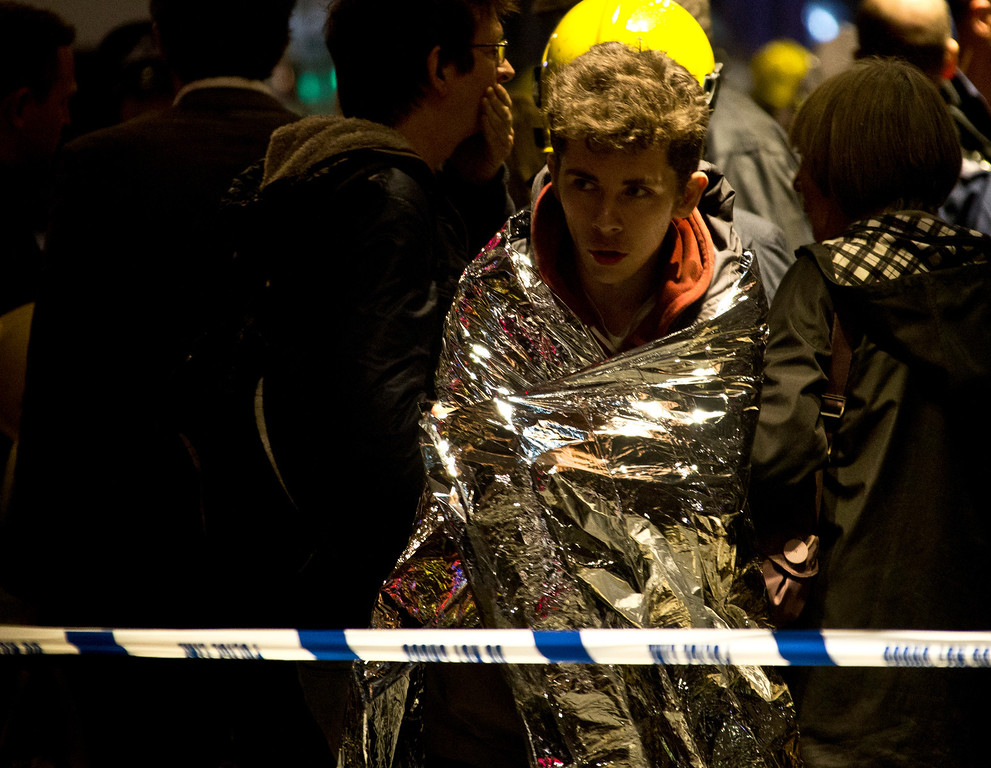 ". A man wraps himself in an emergency foil blanket provided by rescue services following an incident at the Apollo Theatre, in London\'s Shaftesbury Avenue, Thursday evening, Dec. 19, 2013 during a performance , with police saying there were ""a number\"" of casualties. (AP Photo by Joel Ryan, Invision)"