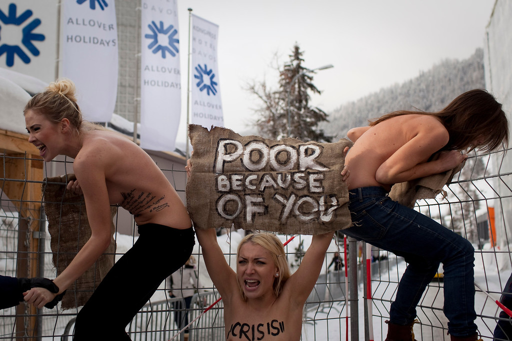 . In this Saturday, Jan. 28, 2012 ile photo made by Associated Press photographer Anja Niedringhaus, topless Ukrainian protesters climb up a fence at the entrance to the congress center where the World Economic Forum takes place in Davos, Switzerland.  (AP Photo/Anja Niedringhaus, File)