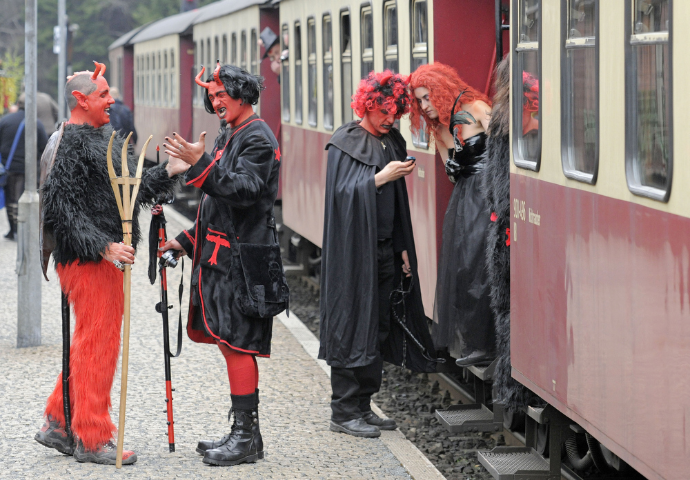 . Men and women costumed as devils and witches stands besides a small train in Schierke, central Germany, Tuesday, April 30, 2013. Hundreds of costumed devils and witches meet to celebrate Walpurgis Night, a traditional religious holiday of pre-Christian origins. The event is named after St. Walburga, an English nun who helped convert the Germans to Christianity in the 8th century. (AP Photo/Jens Meyer)