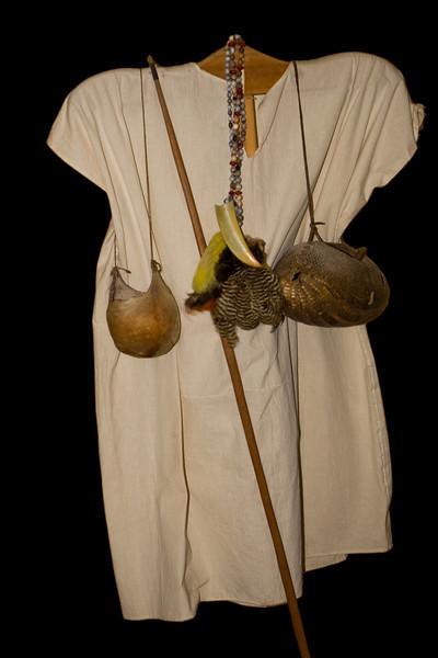 Costume traditionnel des Indiens Lacandons  du  village de NahaHomme, costume du quotidien ,longue chemise blanche. Il porte un sac en carapace de tatou pour conserver les cigares au frais. Il porte les plumes de toucan qu'il offrira à sa femme en cadeau de mariage ,qu'elle portera au bout de ses cheveux et qui permet de distinguer les femmes mariées, avec plumes ,des célibataires sans.