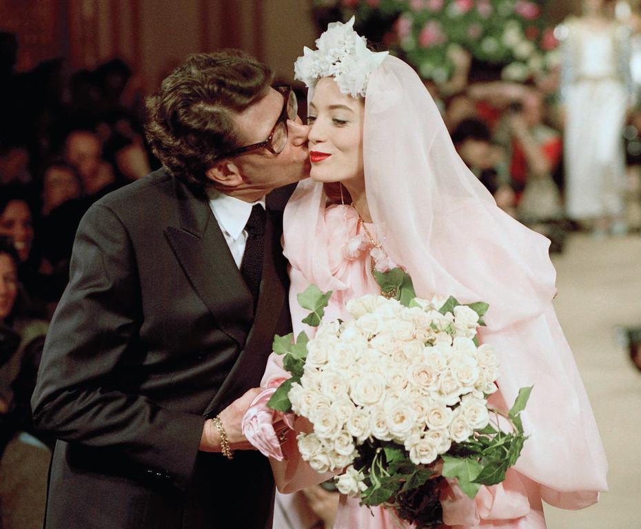 . French fashion designer Yves Saint Laurent embraces his model Lucie de la Falaise, 16, in a wedding dress at the end of the fashion shown presenting Laurent\'s 1990 Spring-Summer haute couture collection in Paris, Jan. 24, 1990. (AP Photo/Lionel Cironneau)