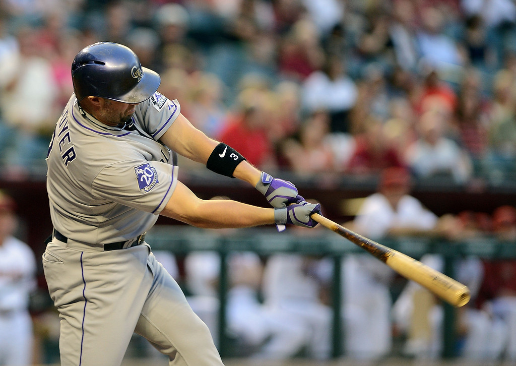 . PHOENIX, AZ - APRIL 26:  Michael Cuddyer #3 of the Colorado Rockies connects for a two-run base hit against the Arizona Diamondbacks in the first inning at Chase Field on April 26, 2013 in Phoenix, Arizona.  (Photo by Jennifer Stewart/Getty Images)