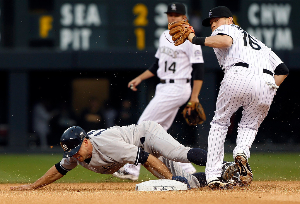 . New York Yankees\' Brett Gardner, front left, slides safely into second base as Colorado Rockies shortstop Reid Brignac, front right, fields the throw and second baseman Josh Rutledge backs up the play in the first inning of a baseball game in Denver on Wednesday, May 8, 2013. (AP Photo/David Zalubowski)