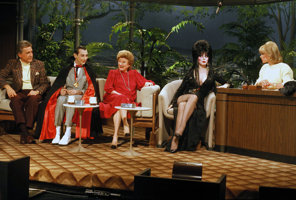 """. Doc Severinsen, left, and Joan Rivers, right, greet Halloween guests to \""""The Tonight Show,\"""" in Los Angeles, Oct. 31, 1985.  The guests are Pee Wee Herman as Count Dracula; Phyllis Diller as Dr. Ruth Westheimer; and Elvira (Cassandra Peterson) as herself.  (AP Photo) No Sales"""