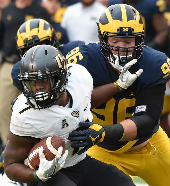 Michigan's Ryan Glasgow tackles UCF's Dontravius Wilson.