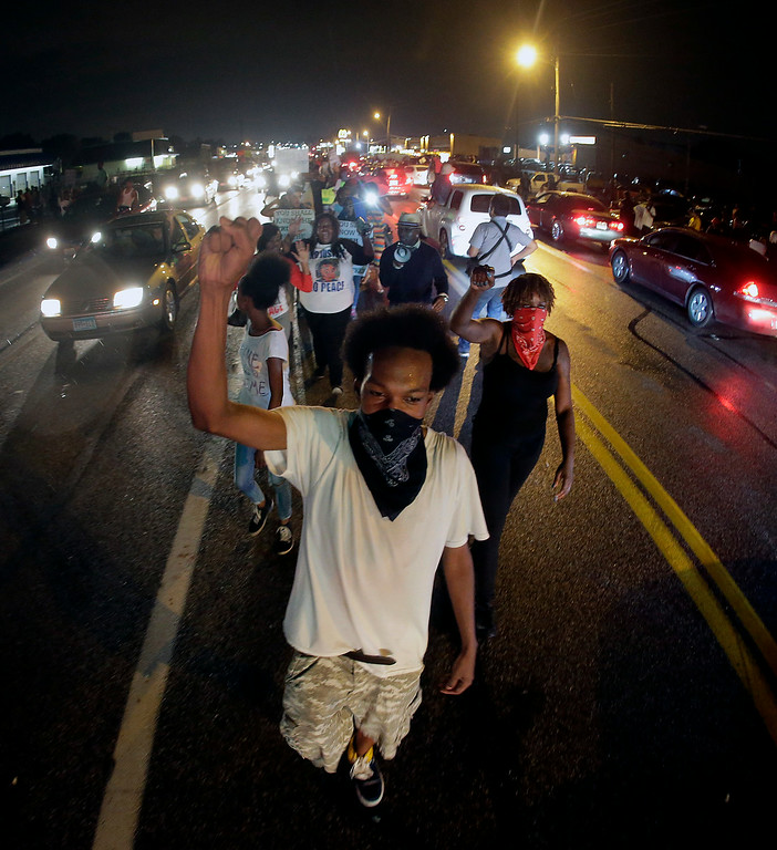 . Protesters march down the middle of a street, Friday, Aug. 15, 2014, in front of a convenience store that was looted and burned following the shooting death of Michael Brown by police nearly a week ago in Ferguson, Mo. (AP Photo/Charlie Riedel)