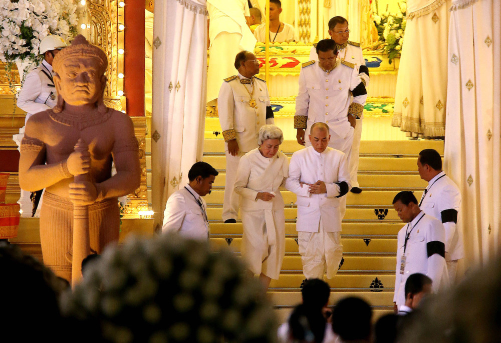". Cambodian King Norodom Sihamoni, center right, son of the late King Norodom Sihanouk, and his mother, Queen Norodom Monineath, center left, with Cambodia\'s Prime Minister Hun Sen, behind Sihamoni, leave the crematorium where the body of Sihanouk rests in Phnom Penh, Monday, Feb. 4, 2013. Hundreds of thousands of mourners gathered in Cambodia\'s capital Monday for the cremation of Sihanouk, the revered ""King-Father,\"" who survived wars and the murderous Khmer Rouge regime to hold center stage in the Southeast Asian nation for more than half a century.(AP Photo/Wong Maye-E)"