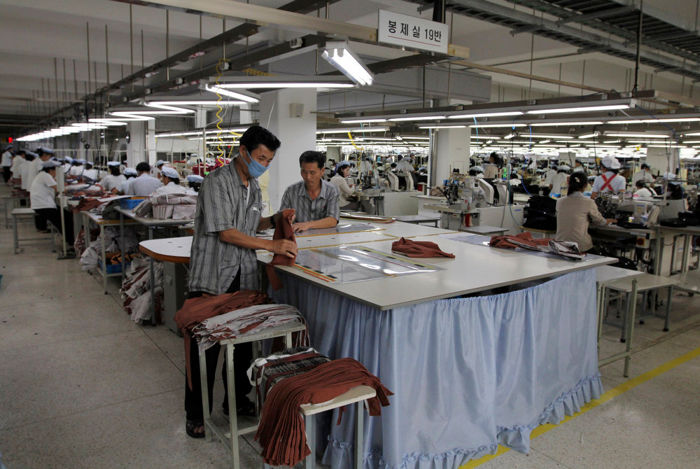 . In this photo taken on Sept. 21, 2012, two North Korean men working for ShinWon, a South Korean clothing maker, prepare garments for production at a factory in Kaesong, North Korea. Since April 3, North Korean authorities have barred South Koreans, including ShinWon managers, from entering North Korea through the Demilitarized Zone to get to the Kaesong industrial complex where some 120 South Korean companies run factories employing North Korean workers. (AP Photo/Jean H. Lee)