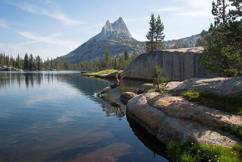 Diving into a quiet mountain lake under the iconic Cathedral Peak in Yosemite National Park.