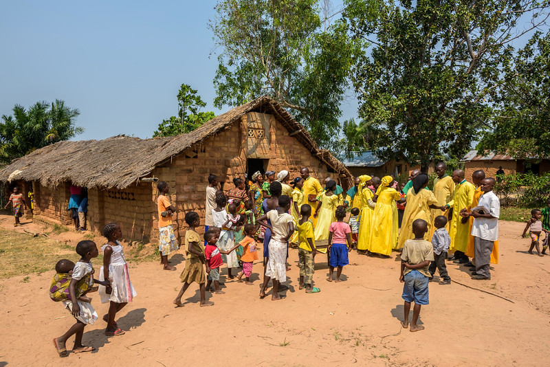 """The congregation gathers outside after Sunday morning worship at Le Lumiere Church, which Grace Mukoma, 10  yr-old boy, and his mother Mbombo Elize and his sister, Harriet, attend, in Central Kasai Province, Kananga, DRC.  Grace's family go to a church called Le Lumiere, The Light. He says, """"I like to sing. When the pastor finishes preaching we sing.""""   Grace sings us a song: """"God the Almighty, descend down and help us. Without your help we can do nothing. Come down and help us.""""  Church on Sunday is loud and energetic. The room is packed. It's a special day because new members are being inducted into the church.  Towards the end of the service, the pastors circle Grace and say a special blessing.   Background Grace lives with his widowed mom, Mbombo Elize, sister Harriet, 7, and an extended family of relatives, including his widowed grandmother, Kapinga Godelive, 66.  Mbombo has had 4 children, the first when she was 15. 2 died during the time they had to run away because of the war. Now it's just Grace and his sister Harriet, 7.  They live in the Kasai Centrale province in a place called Katoka. It's a rural community. Grace and his family had to run when war broke out in the DRC.  His father was killed. His mother and her 4 children ran about 2 kilometers down the road from his house towards the Lualua River. They hid there for about 3 months. Unfortunately, because of a lack of food and disease, Grace's brother and a sister died. After about 3 months Grace and his family hesitantly made their way back to their house. It had been burnt and was empty. They've struggled ever since.    Here's a look at Grace's life today:  Home Life  """"Early in the morning I sweep the compound. Then I wash and if there is food I eat. Then I join my friends at the CFS."""" """"Sometimes they send me on other errands. If they need something, they send me.""""  Food Grace's family doesn't have enough food. On any given day they may or may not eat. When they do eat, it's once a day, usually in th"""