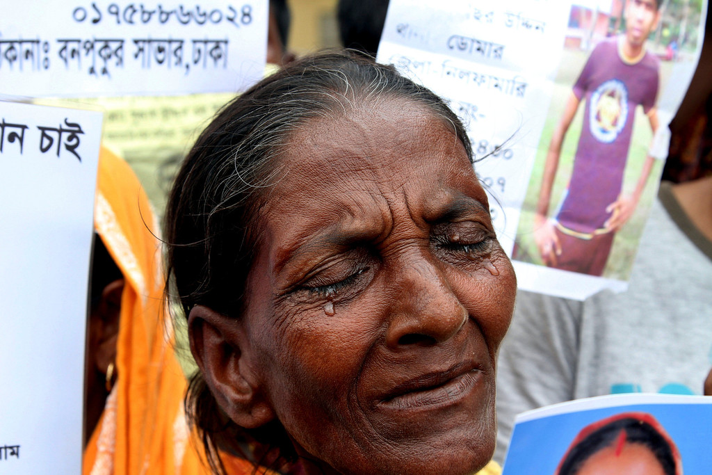 . A Bangladeshi woman weeps as Bangladeshi people hold photographs of their relatives whom they believe are trapped in the rubbles of a building that collapsed in Savar, outskirts of Dhaka, Bangladesh, Tuesday, April 30, 2013.  (AP Photo/Palash Khan)