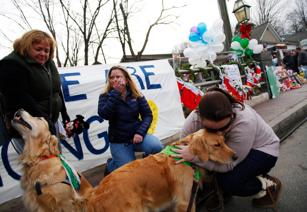 Description of . Comfort dogs Cali (R) and Libby receive attention from women near a memorial for the Sandy Hook Elementary School shooting victims in Newtown, Connecticut December 20, 2012. Even as they buried more victims of the second-deadliest school shooting in U.S. history on Thursday, residents of Newtown, Connecticut, looked for ways to pressure national leaders to restrict access to weapons. REUTERS/Joshua Lott