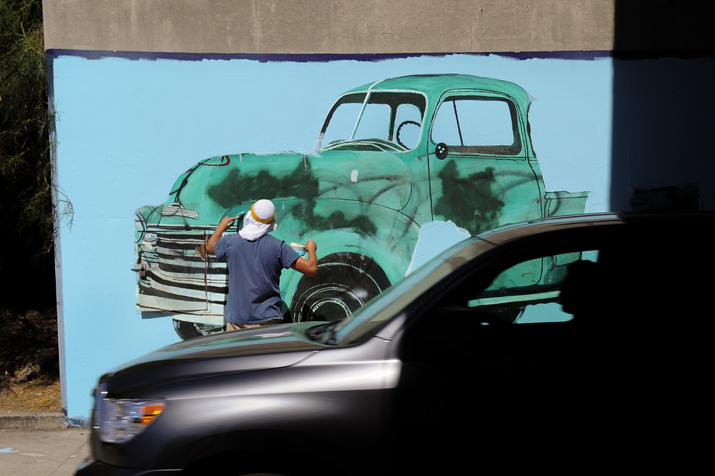""". Cars whiz by Jeff Lingle painting the restoration of the mural \""""Panorama: G.M. Recollections from the Past,\"""" on Van Nuys Boulevard in Panorama City, Thursday, June 20, 2013. The original mural was painted by Alfredo Diaz Flores in 1998 and pays homage to the General Motors plant that used to be near the mural site. (Michael Owen Baker/Staff Photographer)"""