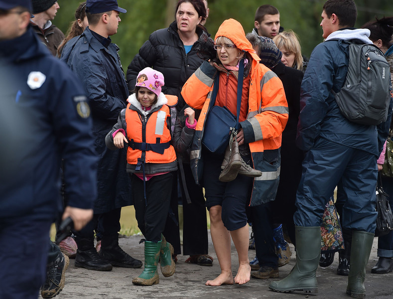 ". People evacuated from their flooded houses cross a bridge in the town of Obrenovac, 40 kilometers west of Belgrade, on May 17, 2014. Deadly floods across Bosnia and Serbia have claimed at least 14 lives and led to the evacuation of 15,000 people after the Balkans suffered its heaviest rainfall in a century, officials said today. In Serbia, ""rescuers have started recovering dead bodies from flooded areas, but we will not make the number public before the complete withdrawal of the water,\"" Prime Minister Aleksandar Vucic told reporters. More than 15,000 people have been evacuated from a number of towns throughout Serbia, hit by what Vucic called \""a horrible natural catastrophe.\""  (ANDREJ ISAKOVIC/AFP/Getty Images)"