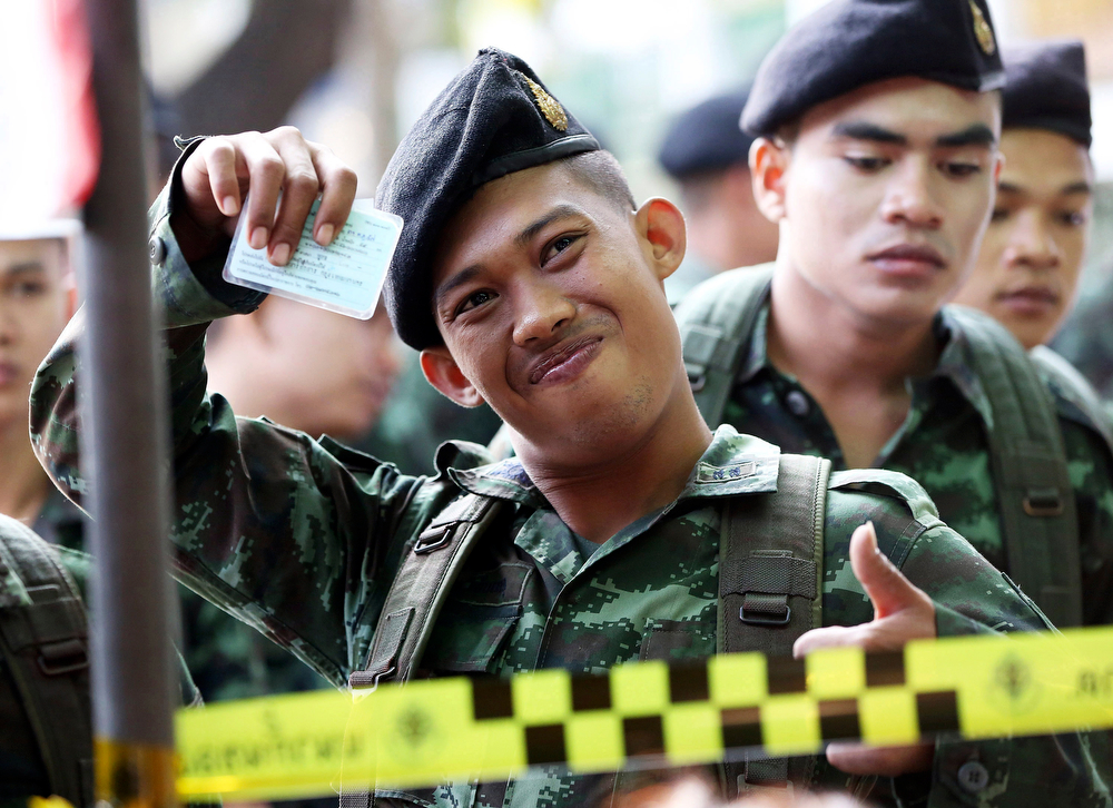 . A Thai soldier shows his identity card while waiting in a queue to vote with his colleagues during the general election at a polling station in Bangkok, Thailand Sunday, Feb. 2, 2014.  (AP Photo/Apichart Weerawong)