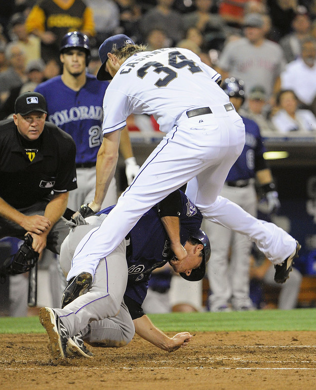 . SAN DIEGO, CA - JULY 10:  DJ LeMahieu #9 of the Colorado Rockies scores ahead of the tag of Andrew Cashner #34 of the San Diego Padres during the fifth inning of a baseball game at Petco Park on July 10, 2013 in San Diego, California.  LeMahieu scored on a wild pitch.  (Photo by Denis Poroy/Getty Images)