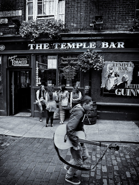 Musician walking past a popular pub in Dublin.