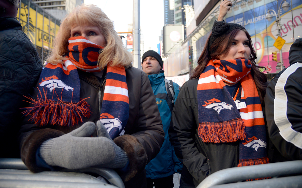 Description of . Super Bowl XLVlll fans Carol Fett (L) and Kelly Fett keep warm with their Broncos scarves as fans hit Times Square  to enjoy the Super Bowl Boulevard. The NFL transformed a portion of Broadway into the sports and entertainment hub of Super Bowl Week, January 29, 2014. (Photo by John Leyba/The Denver Post)