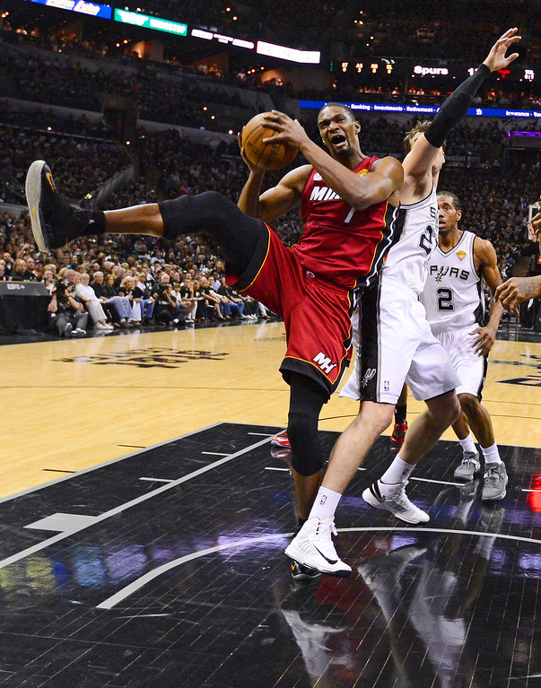 . Miami Heat\'s Chris Bosh (1) grabs a rebound against San Antonio Spurs\' Tiago Splitter (22), of Brazil, during the second half at Game 3 of the NBA Finals basketball series, Tuesday, June 11, 2013, in San Antonio. (AP Photo/John G. Mabanglo, Pool)