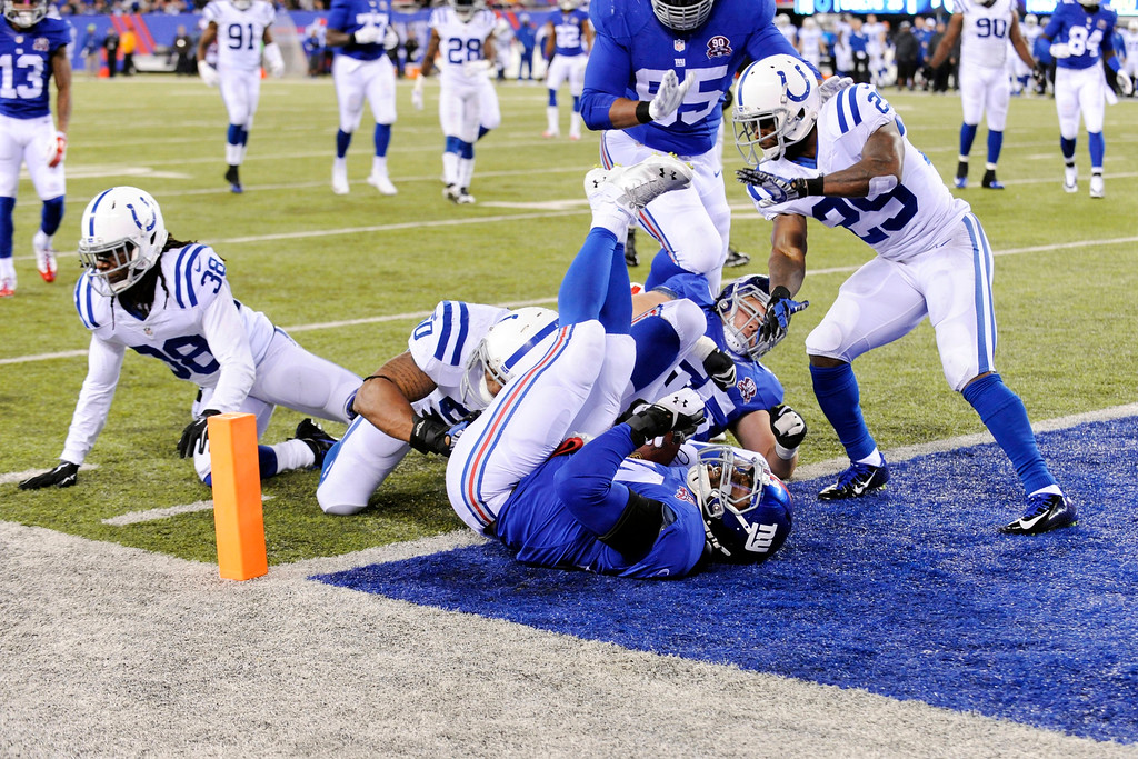 . New York Giants running back Andre Williams, front center, scores a touchdown as Indianapolis Colts\' Mike Adams (29) and Sergio Brown (38) react during the second half of an NFL football game Monday, Nov. 3, 2014, in East Rutherford, N.J.  (AP Photo/Bill Kostroun)