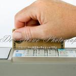 A hand sliding a credit card through a credit card termial slot.