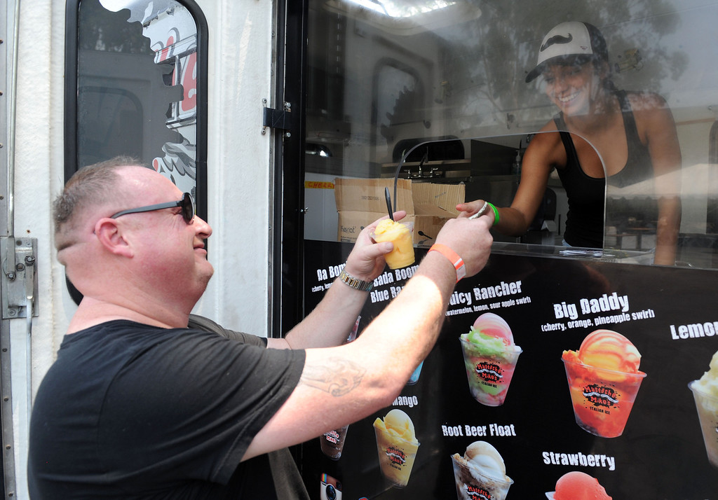 . (John Valenzuela/Staff Photographer) Brian Huerra of Redlands takes his Italian Ice from Mustache Mike\'s Brittany Guerra during the second annual Food Truck and Brewfest in Redlands Saturday, June 29, 2013.
