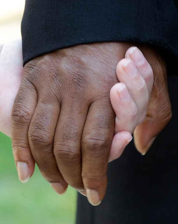 """. People of mixed races hold hands during a prayer outside the Dexter Ave. King Memorial Baptist Church in Montgomery, Ala., Wednesday, Aug. 28, 2013. Members were holding a bell ringing ceremony to honor the 50th anniversary of the \""""I Had a Dream\"""" speech by Rev. Martin Luther King Jr., who was pastor of the church in 1954. (AP Photo/Dave Martin)"""