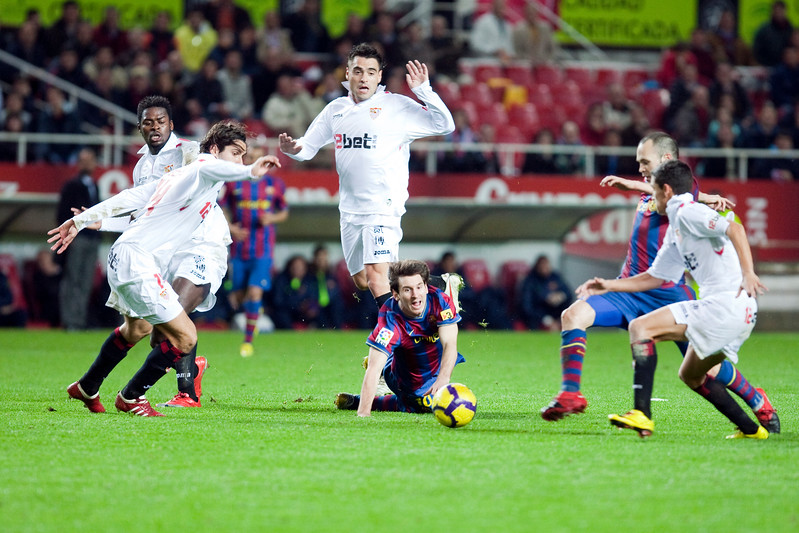 Messi falling down and looking at the ball. Spanish Cup game between Sevilla FC and FC Barcelona, Ramon Sanchez Pizjuan stadium, Seville, Spain, 13 January 2010
