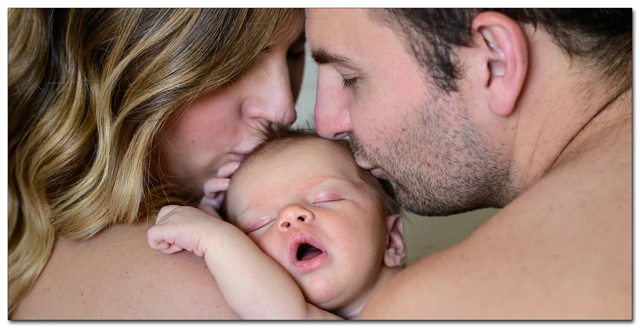 mother and father kissing newborn during maternity session