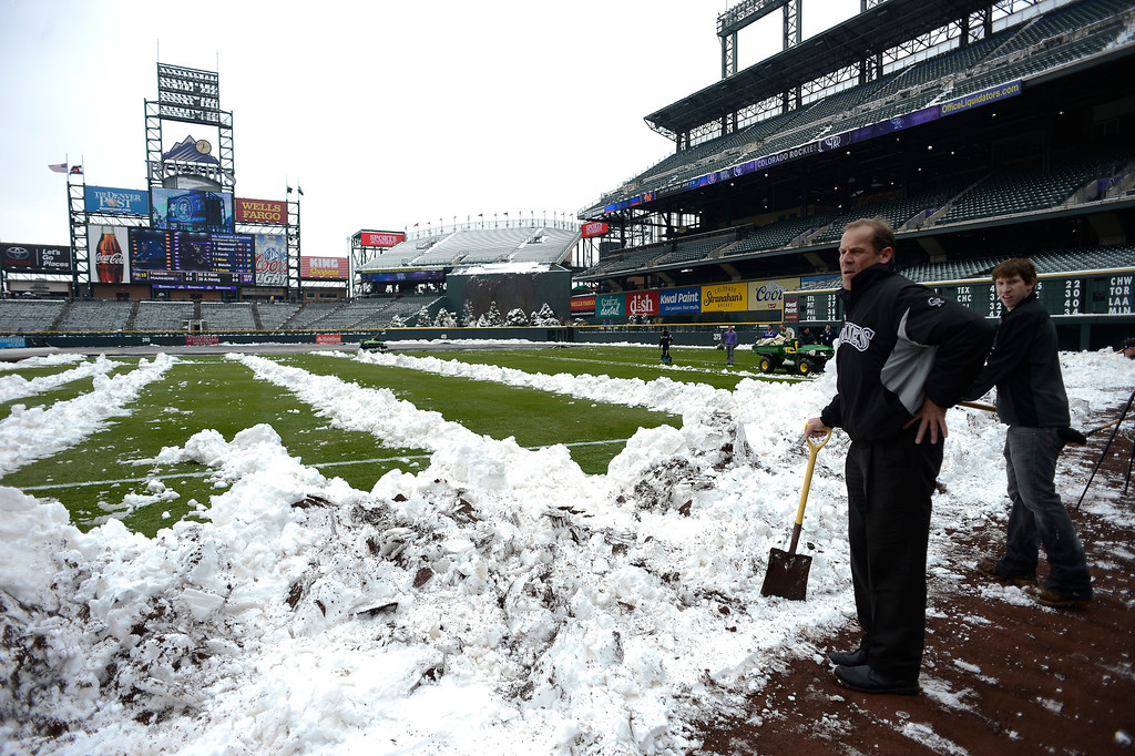 . Dick Monfort, Owner, looks on as he takes a break from shoveling snow doen the right field line. Rockies grounds crew and employees work to clear the field of snow to get the first game of a double header in against the New York Mets April 16, 2013 at Coors Field. (Photo By John Leyba/The Denver Post)